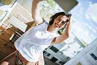Smiling young woman taking a selfie on balcony with tablet - KIJF01486