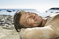 Portrait of man relaxing on sandy beach - PDF01229