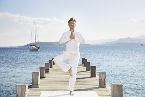Mature man doing yoga exercise on jetty - PDF01232
