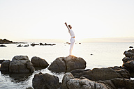 Mature man doing yoga exercise on a rock at the sea - PDF01238