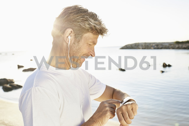 Mature man with earphone checking his smartwatch after yogging on the beach - PDF01241
