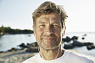 Portrait of confident mature man with earphones on the beach - PDF01247