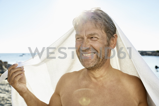 Portrait of smiling man with towel in front of the sea - PDF01256