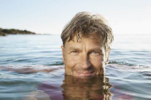 Portrait of smiling man bathing in the sea - PDF01259