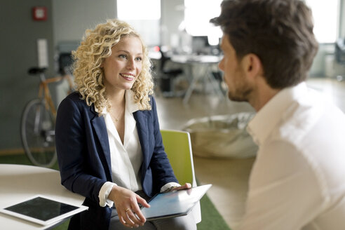 Businessman and woman discussing project in office, using digital tablet - PESF00572