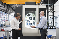 Two men looking at machine on factory shop floor - DIGF02447