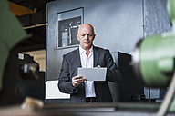 Man with tablet at machine on factory shop floor - DIGF02465