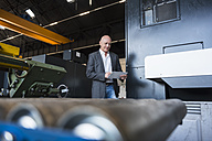 Man with tablet at machine on factory shop floor - DIGF02468
