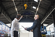 Two businessmen with clipboard on factory shop floor with bridge crane - DIGF02474