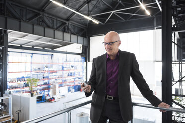 Businessman with cell phone on factory shop floor - DIGF02480