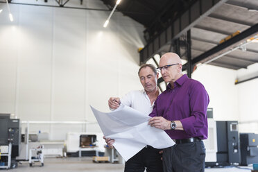 Two businessmen looking at plan in factory shop floor - DIGF02486