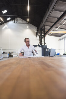 Man with plan, product and laptop on table in factory - DIGF02489