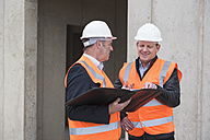 Two men wearing safety vests talking on construction site - DIGF02507