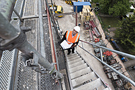 Man wearing safety vest on scaffolding on construction site - DIGF02516