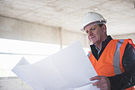 Man with plan wearing safety vest in building under construction - DIGF02522