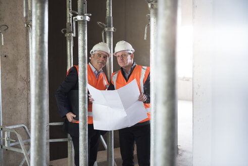 Two men with plan wearing safety vests in building under construction - DIGF02525