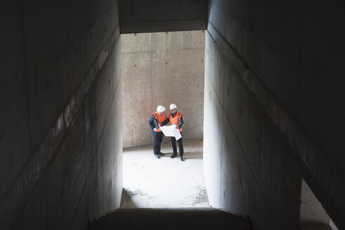 Two men with plan wearing safety vests talking in building under construction - DIGF02531