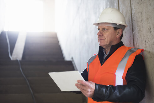 Man with tablet wearing safety vest in building under construction - DIGF02534