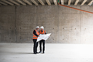 Two men with plan wearing safety vests talking in building under construction - DIGF02537