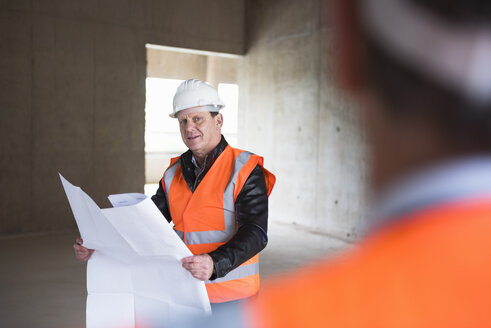 Man with plan wearing safety vest in building under construction - DIGF02540