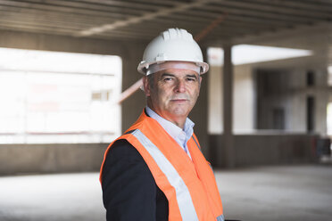Portrait of man wearing safety vest in building under construction - DIGF02543