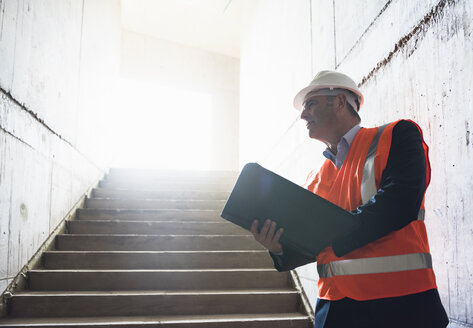 Man with documents wearing safety vest in building under construction - DIGF02549