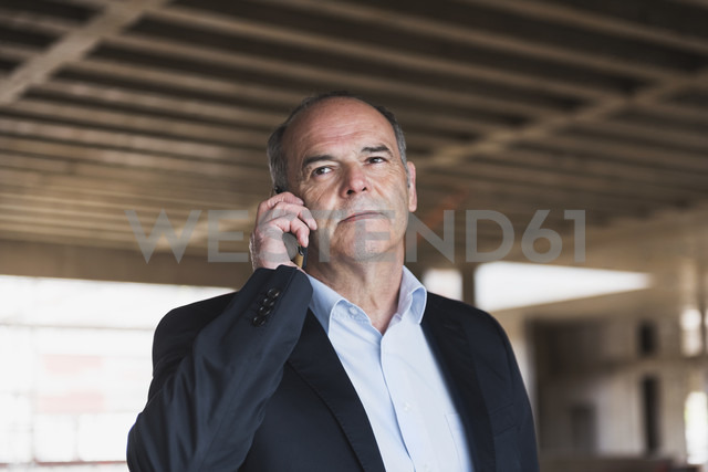 Businessman on cell phone in building under construction - DIGF02555