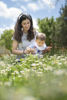 Mother and baby son on blossoming field of flowers in spring - JASF01781