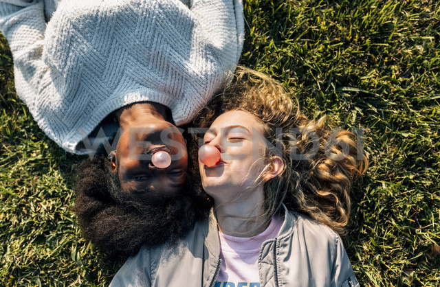 Two best friends making a gum bubble lying in the grass - MGOF03358 - Marco Govel/Westend61
