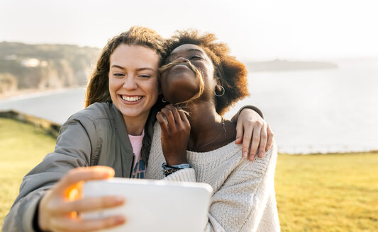 Two happy best friends making a selfie at the coast - MGOF03364
