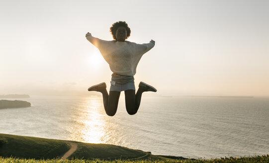 Young woman jumping at the coast at sunset - MGOF03388