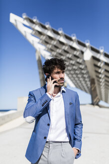 Young businessman on smartphone outdoors - GIOF02566