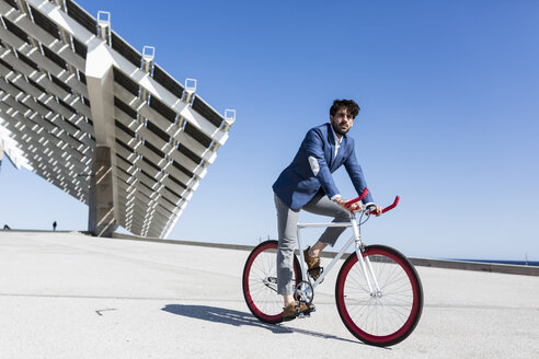 Young businessman on fixie bike outdoors - GIOF02572