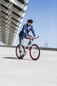 Young businessman on fixie bike outdoors - GIOF02575