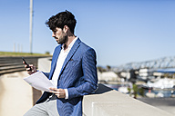 Young businessman with smartphone and documents outdoors - GIOF02584