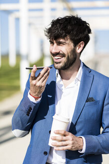 Happy young businessman with smartphone and takeaway coffee outdoors - GIOF02593