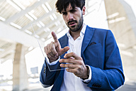 Young businessman using futuristic portable device - GIOF02596