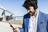 Young businessman wearing headphones looking at smartphone outdoors - GIOF02602