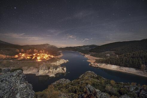 Spain, Castilla y Leon, Palencia, starry night over small village and lake Camporredondo - DHCF00072