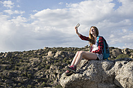 Spain, Madrid, young woman resting on a rock taking a selfie during a trekking day - ABZF02000