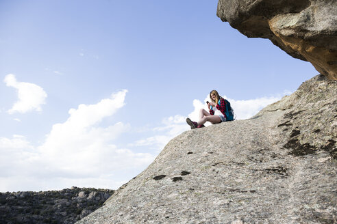 Spain, Madrid, young woman resting on a rock using her phone during a trekking day - ABZF02003