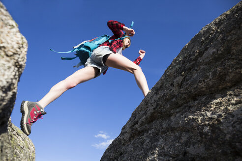 Spain, Madrid, young woman jumping between rocks during a trekking day - ABZF02006