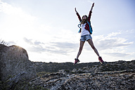 Spain, Madrid, young woman jumping during a trekking day - ABZF02009