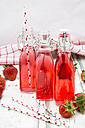Three glass bottles of homemade strawberry lemonade and strawberries on white wood - LVF06104