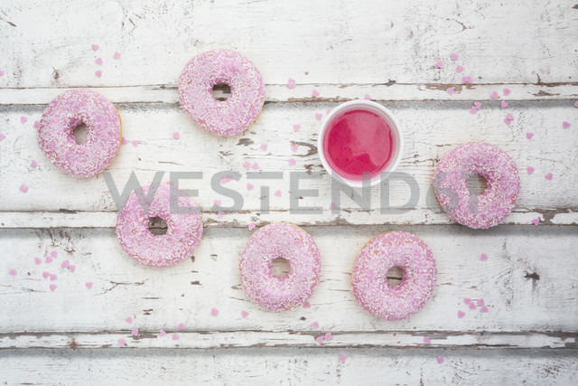 Six doughnuts with pink icing and sugar granules on wood - LVF06107