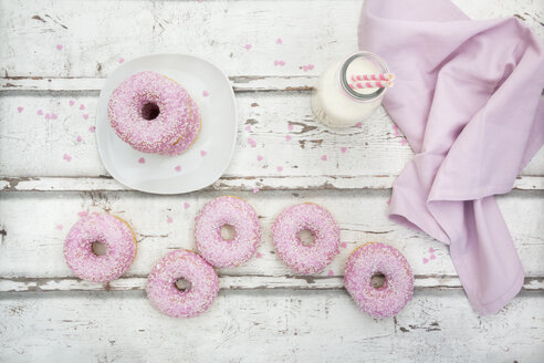 Doughnuts with pink icing and sugar granules and a bottle of milk on wood - LVF06113
