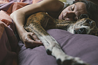 Woman lying in bed with her dog - SKCF00294
