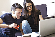 Young couple with credit card using laptop in the living room - FMOF00276