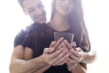 Hands of young couple holding cup of coffee - FMOF00279