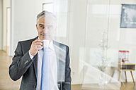 Mature businessman standing in office, drinking coffee - FMKF04114